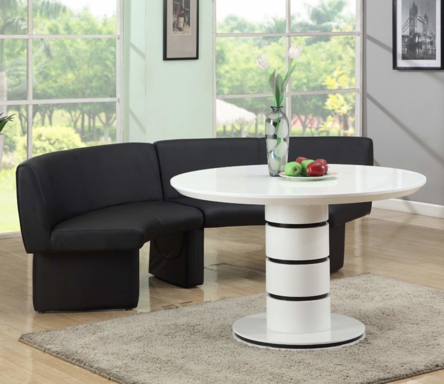 If your room needs something sleek, modern, and unique, look no further. This high contrast contemporary dining set features a curved bench seat upholstered in black faux leather, set against a glossy white wood table with circular top and pedestal base. Black stripe accents add an additional layer of nuance.