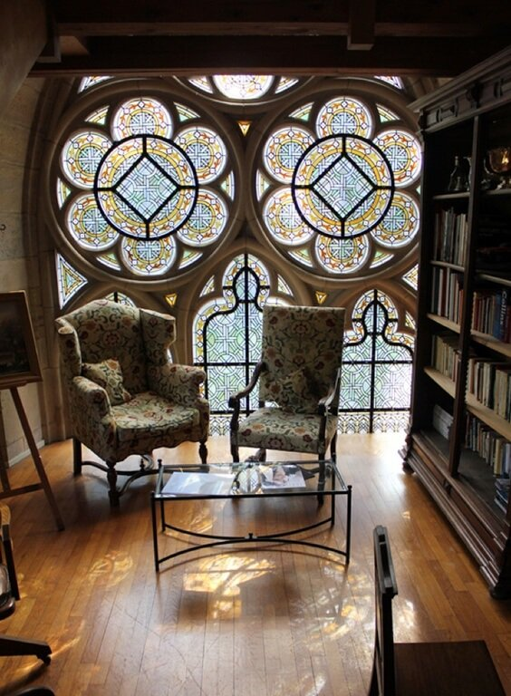 This room has large stained glass windows that cover the entirety of the far wall. The intricate patterns on the glass are symmetrical and uniform. The colors incorporated help to reflect various shades of light into the room.