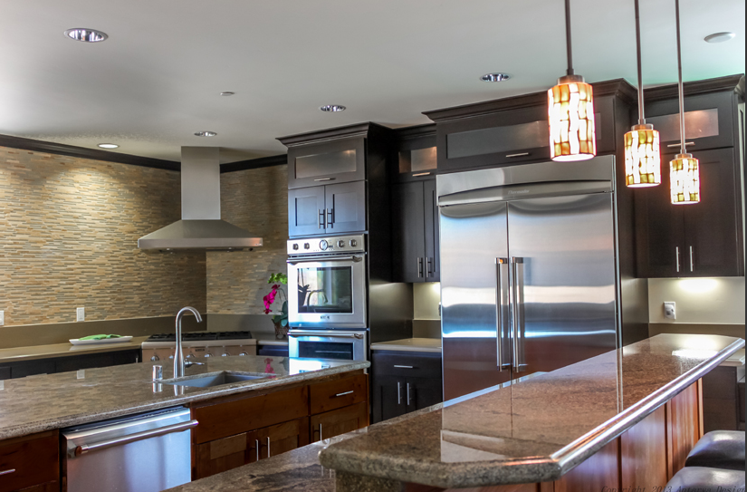 The first thing that stands out in this traditionally styled kitchen is the sleek appearance of stainless steel appliances, contrasting with the dark wood cabinetry. A massive textural backsplash at left adds fresh detail, while granite countertops mesh perfectly.