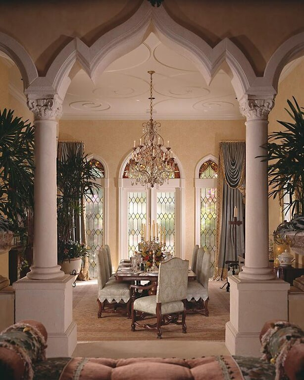 This dining room is framed by two large white columns. There is a extravagant chandelier hanging above the dining table, with frosted stained glass beyond that lets in the natural light.