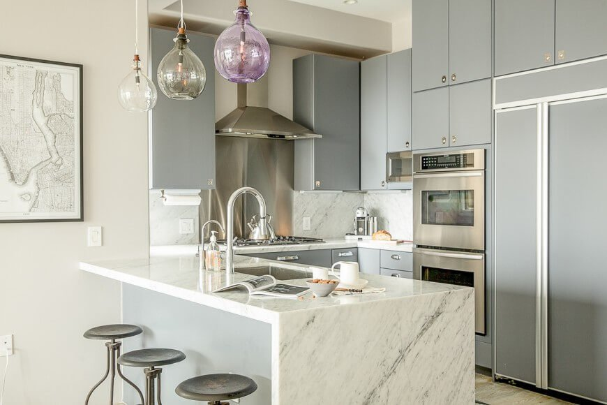 This cozy but open kitchen is defined by the pairing of sleek grey cabinetry and white marble countertops. The appearance of stainless steel appliances subtly matches the flush hardware on the cupboard doors.