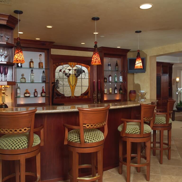 This bar is furnished with rich wooden chairs that match the material on the bar and the shelving unit. There is a section of stained glass in between the two shelving units, which accents the space well.