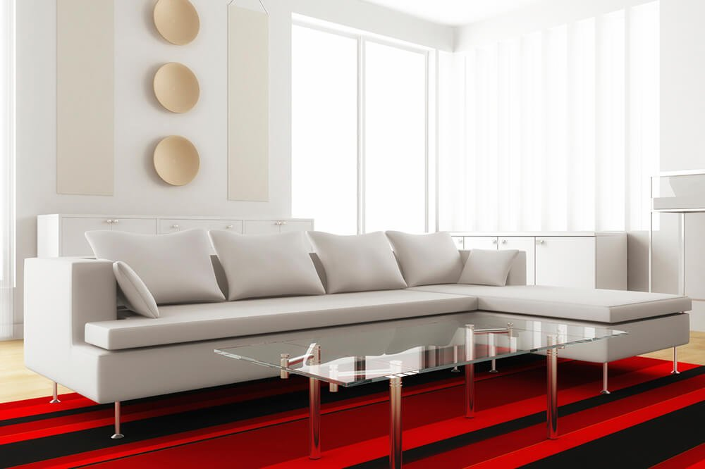This living room features a white couch with sharp right angles. The chrome silver table legs match that of the couch legs, while the red and black rug beneath is a vibrant contrast for the rest of the white room.