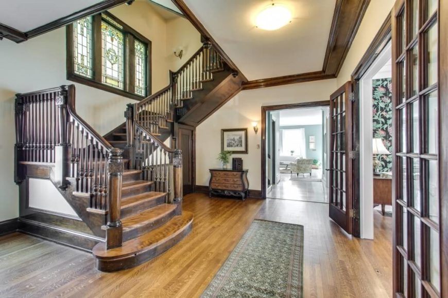 This grand foyer is covered with rich stained wood on the floor, and a large dark wooden staircase to match. Complimenting the style is a large sectional window featuring stained glass. The green tones match the rug and other accent features well.