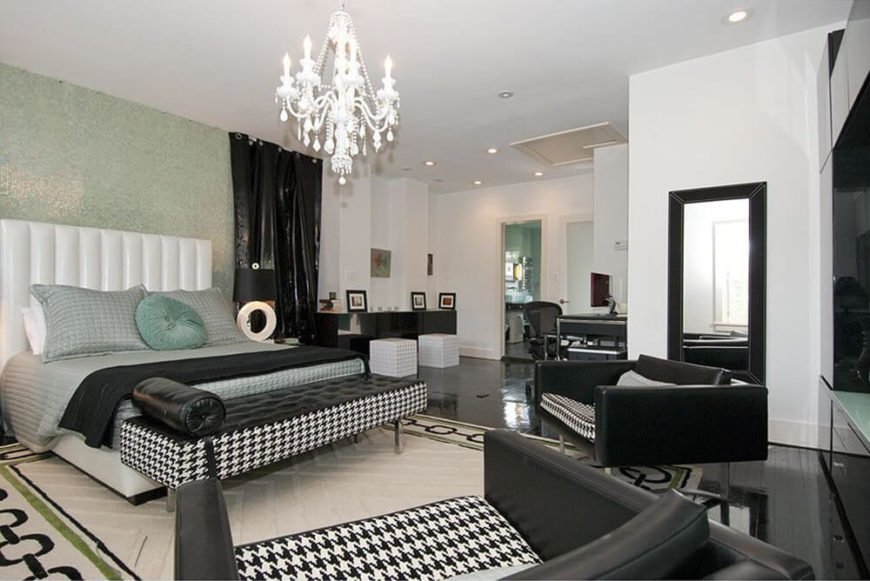 This modern bedroom has a bold black and white color scheme, as well as bold patterns on the furniture. The room is quite spacious overall, an in the corner before the bathroom entrance, there is a working desk with a computer. This will allow the homeowner to conduct business straight from the comfort of the bedroom.