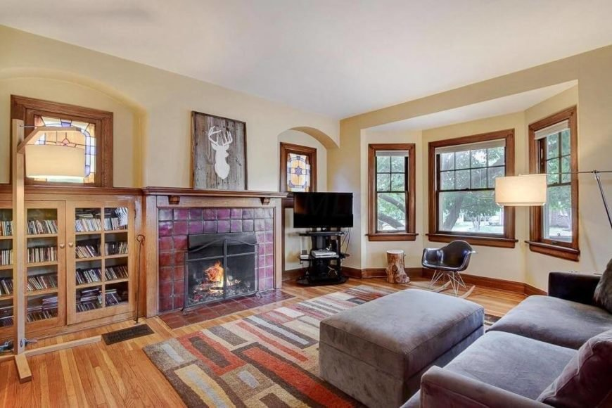 A living room with hardwood floors, and a large area rug before the couch. Just as the rug ends, the fireplace begins, and a red brick tile gives the room a bit of character, by adding some accent coloring.