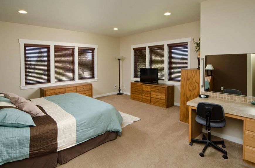 This bedroom features stained wood cabinets and drawers with a defining wood grain. The room itself is quite spacious while the large windows help to let in natural light, with curtains for the added option of darkness. There is a desk to the side with a large mirror directly above it, allowing for the desk to serve both as a vanity and as a working space.