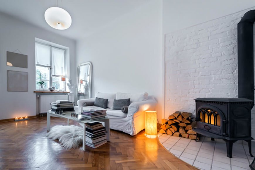 Brick is a lot more flexible than you might think. In this living room, the designer went with white paint throughout, including the brick wall behind the wood stove.