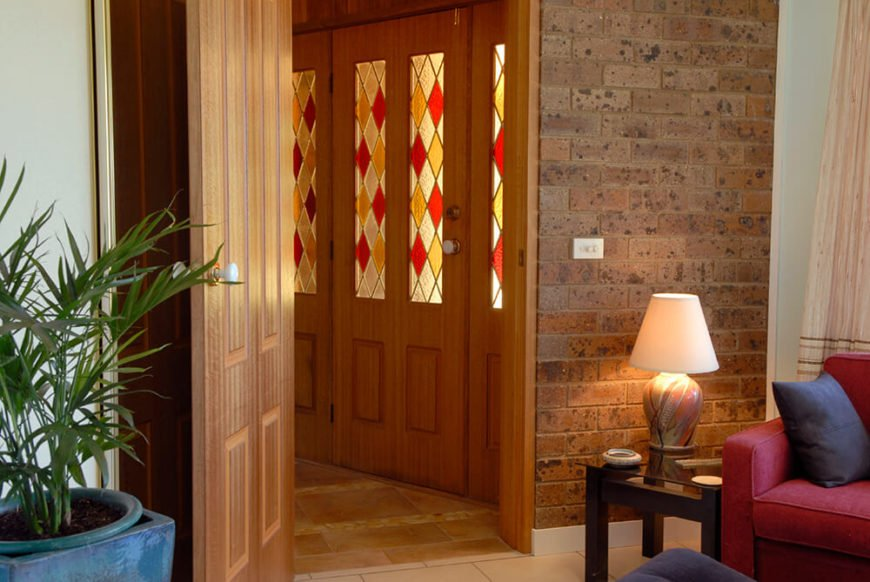 This entryway features rich stained wood doors, transitioning to red brick around the corner. The stained glass panels on the door maintain a low light in the entryway, and compliment the rich wood tones.