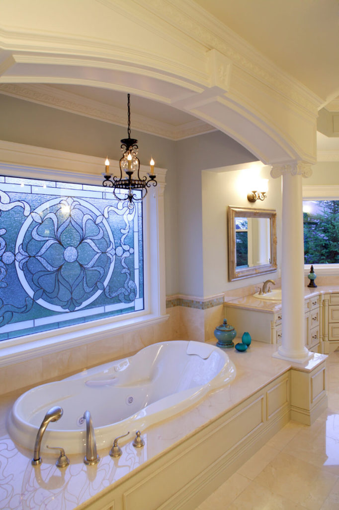 This bathroom is covered with high gloss tile and stone marble. There is a large stained glass window directly above the bath, which lets blue light reflect into the space, creating a calming atmosphere.