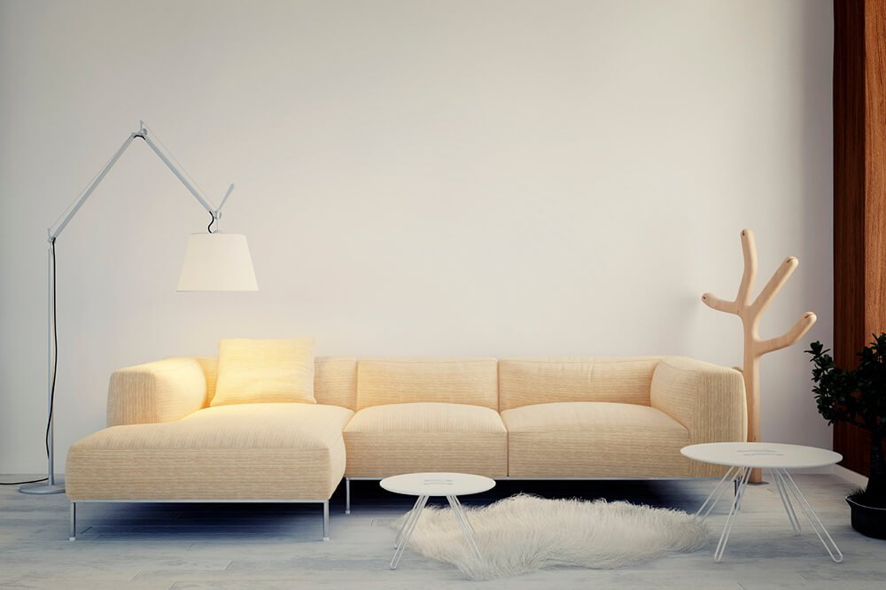 A unique and minimalist design, centered around a light khaki sofa and feathery plush rug. The two white side tables add functionality to the space, while the floor lamp and wooden hat rack frame the couch.