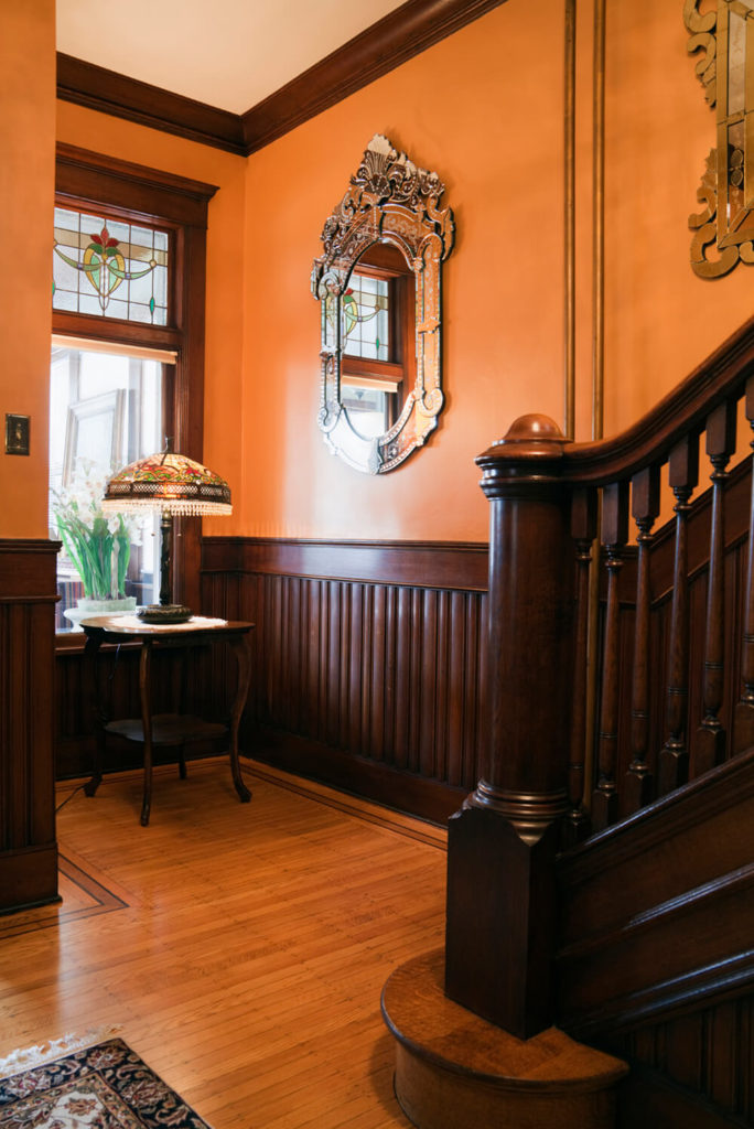 This foyer has a golden stained wood floor, with a deeply stained wood paneling covering the lower third of wall. This contrasts the yellow walls, while the stained glass on the window and lampshade help to balance the colors and tie them all together.