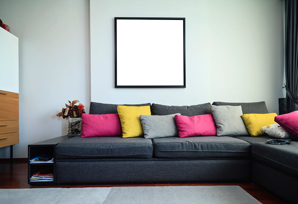 A black couch holds colorful accent pillows, which provide most of the color in this living room. There is a dark richly stained hardwood floor covered by a large grey rug in front of the couch.