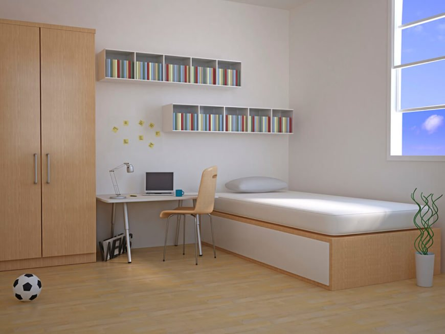 This minimalist bedroom features a bed, a desk, a closet, and small shelving units above the head of the bed and desk. There is one window near the foot of the bed, which lets in some natural light. The bed frame, closet, and desk chair are all made up of a light wood, which compliments the rest of the white room.