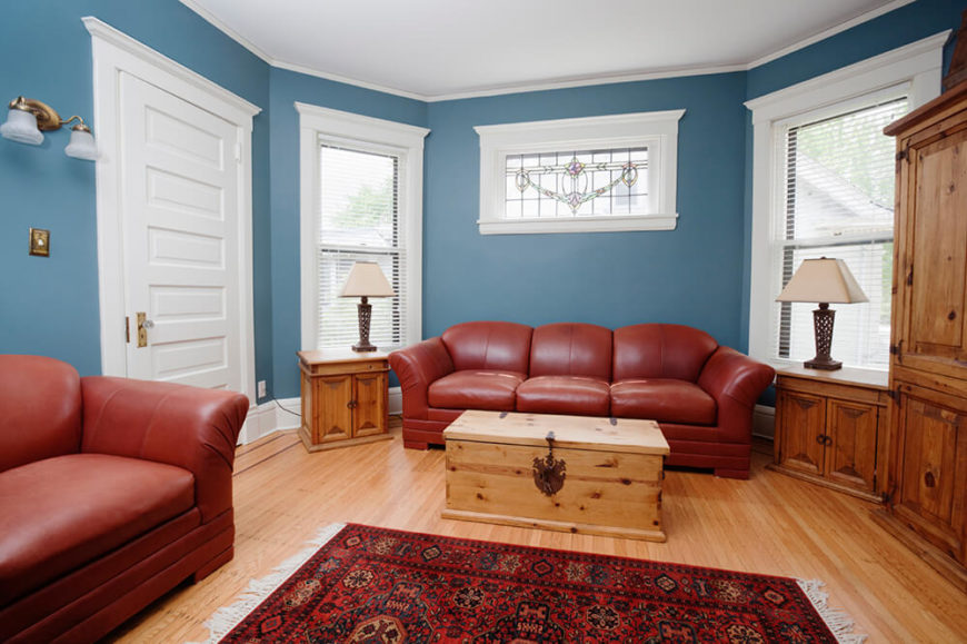 This living room has a hardwood floor, which is covered by an area rug with an intricate design. The furniture is leather and compliments the colors on the rug. Just above the large sofa, there is a stained glass window with a elegant design.