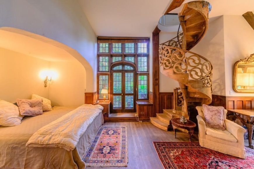 A winding staircase leads down into this bedroom space. The wooden floors match the paneling on the lower quarter of the walls. To the right as you exit the staircase, you will see an exit to the outdoors, covered in stained glass and rich wood.
