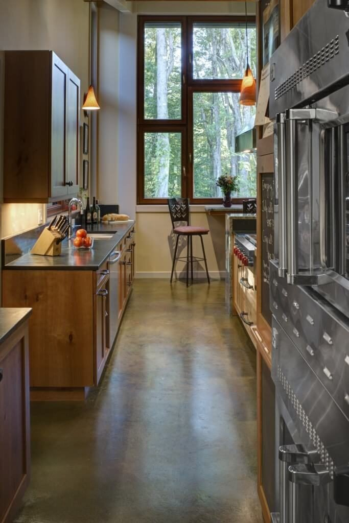 Kitchen featuring stainless steel appliances and wooden cabinetry with pendant lights and a dine-in table set.