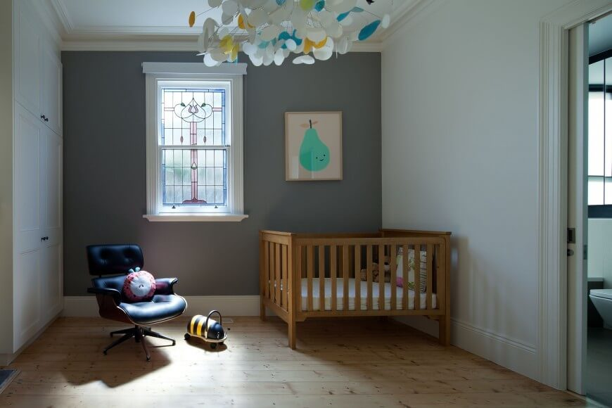 This is a bedroom space that serves as a nursery. The light woodgrain floors match the material of the crib, while the paper chandelier and framed picture add some color to the room. The stained glass is an elegant accent for the space.