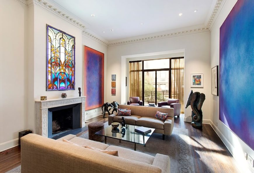 This living room has two large paintings, each providing a great amount of color for the room. In addition to that, there is a stained glass window just above the fireplace, which adds an intricate design element to the space.