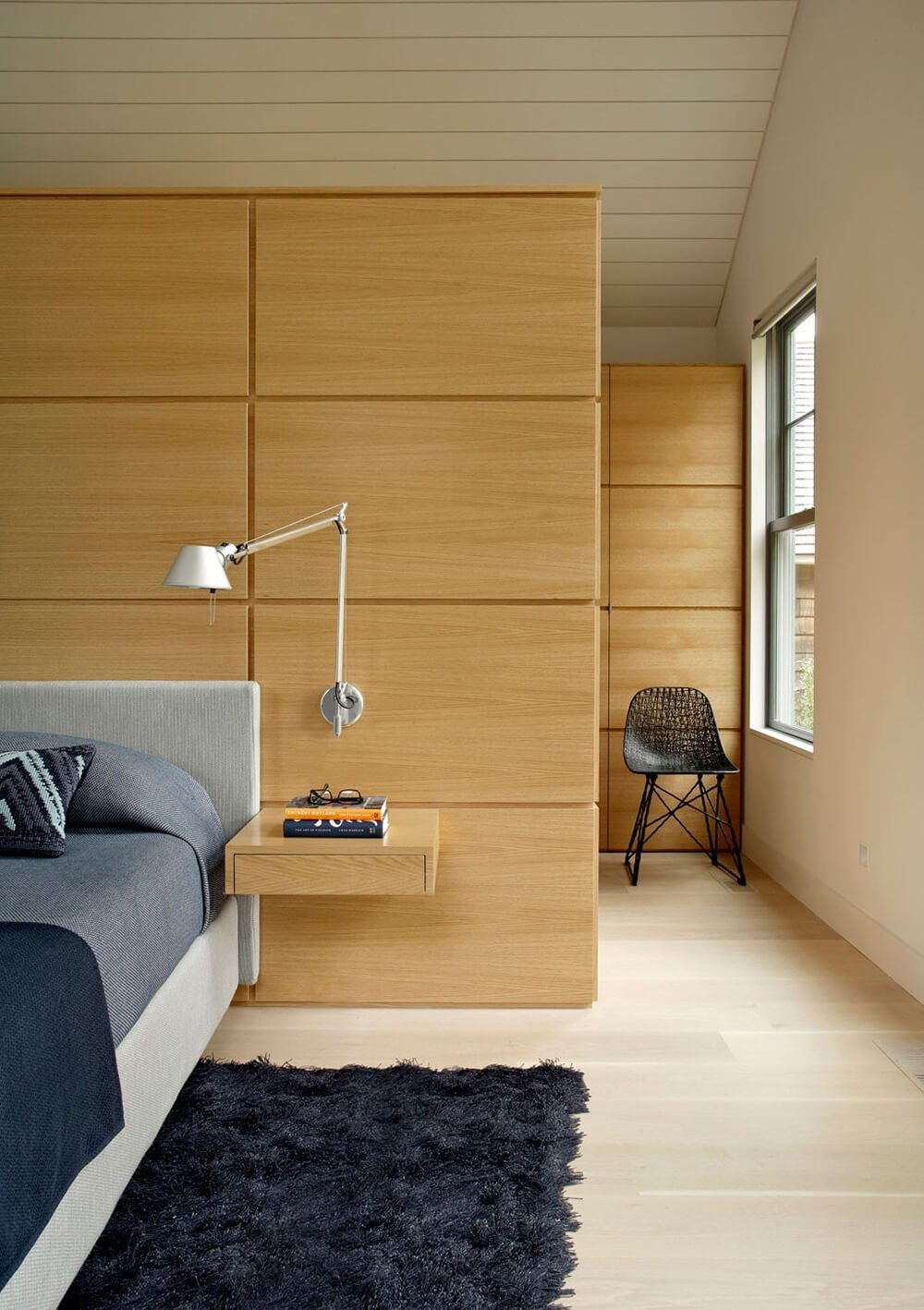 In the bedroom of this house, the light hardwood floor remains prevalent. The walls have a rich glossed wood paneling that compliments the hardwood floors and the dark blue furnishings in this room. We can recognize a modern style from the unique bedside shelf, as well as from the adjustable lamp mounted to the wall.