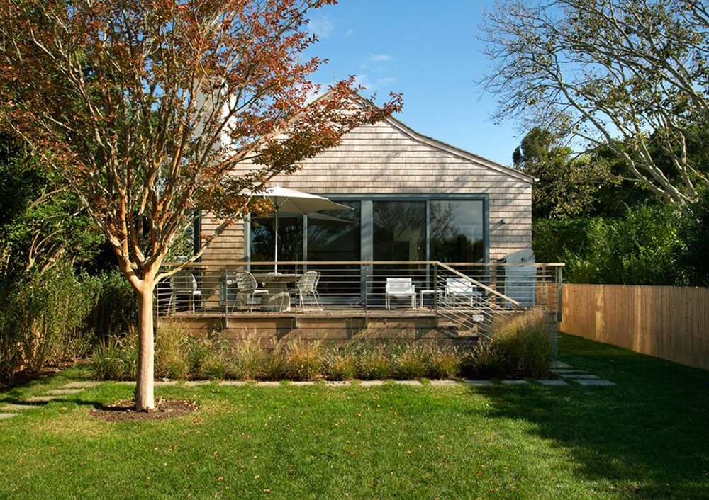 This exterior view of the home reveals that while it is small, the backyard of this property is open and spacious enough to accommodate a reasonable number of guests. There is a large square stone path leading from the deck, and around the perimeter of the yard, this helps to create a division between the flower beds and the actual yard.