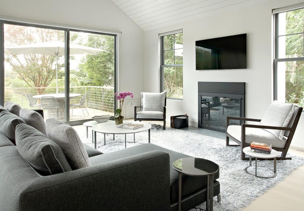 This angle gives us a full view of the living room, in which you will notice the television above the fireplace, two lounging chairs, and the large couch facing the fireplace. There are windows on each side of the TV and fireplace, as well as a large glass sliding door leading to an outdoor deck.