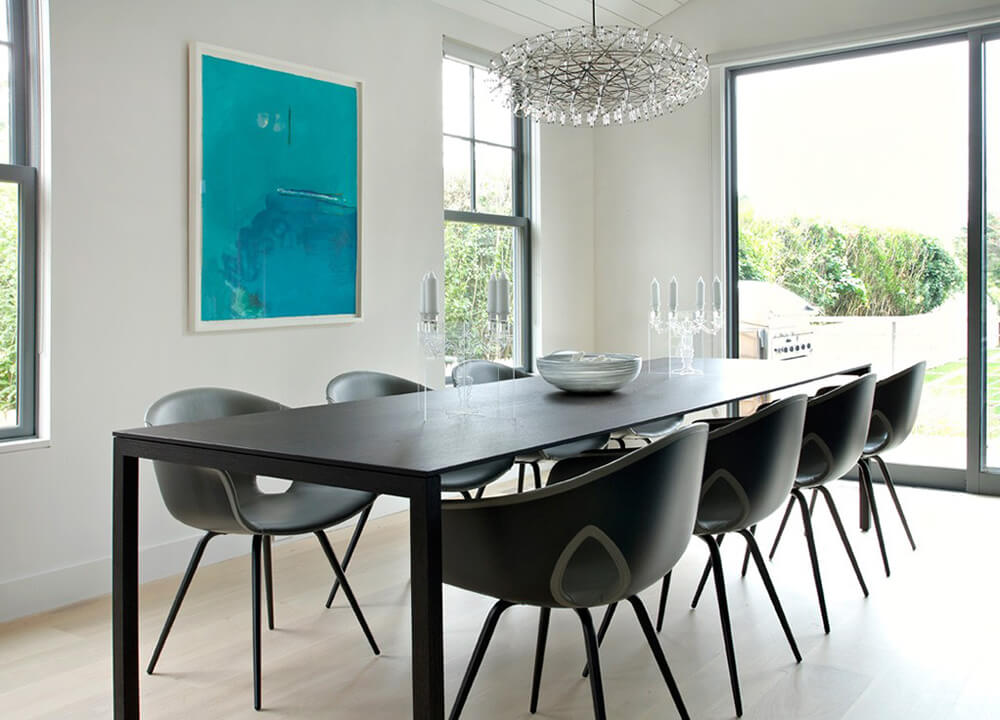 The dining area in this home features elegant candle holders that are transparent, as not to cut off any interaction between those sitting across the table from each other. The table itself is long and sleek, featuring matching chairs that are modern in style. A unique chandelier hangs directly above this space, and vibrant artworks helps to contrast the colors in the space.