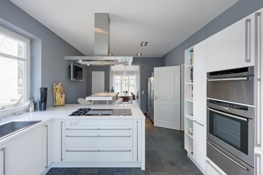 Kitchen with smart appliances and white cabinetry along with smooth white countertops and tiles flooring.