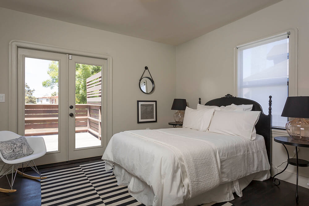The primary bedroom also features a set of glass French doors for easy and direct access to the deck and the outdoors. The simple white room is enlivened with a corner accent chair in the same white and natural wood style as the dining set.