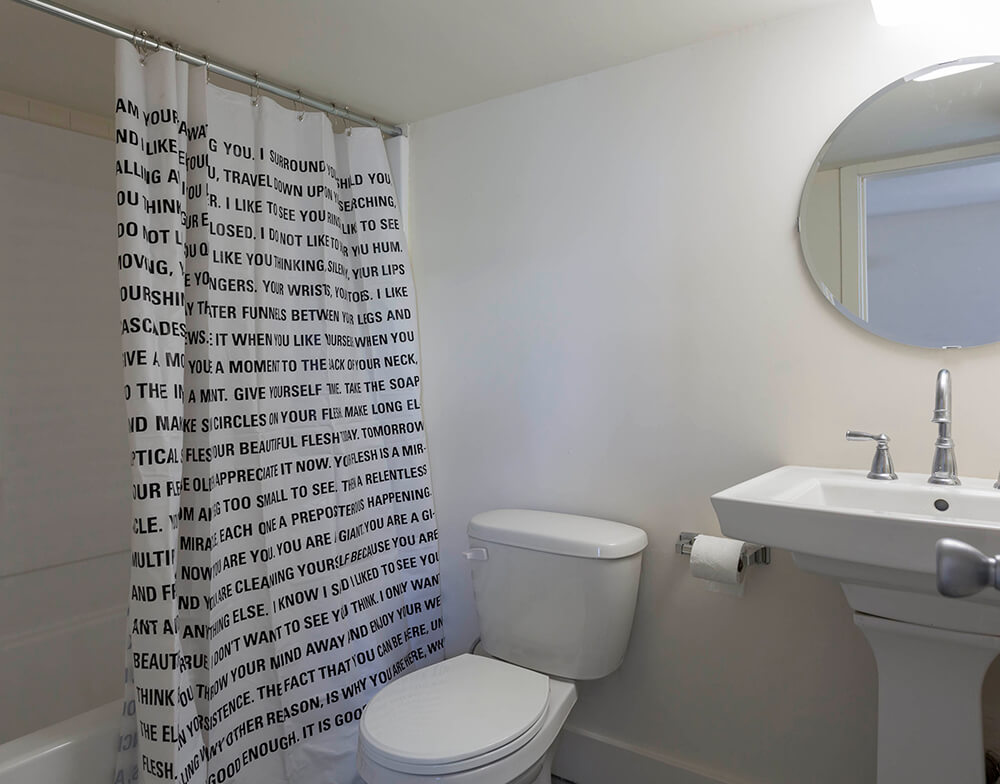 The second bathroom enjoys a more traditional setup, with a pedestal sink beneath a small round mirror. However, a unique inspirational shower curtain offers a unique touch.