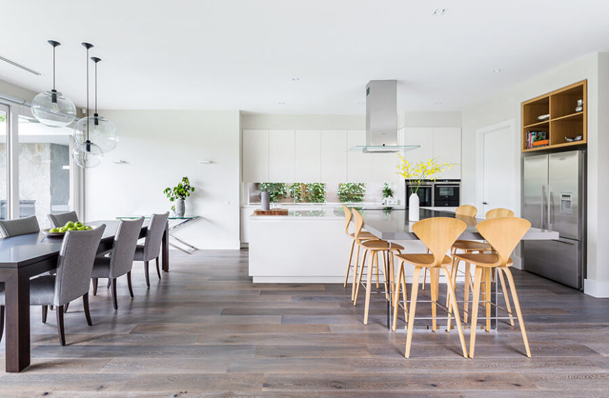 Large L shape kitchen with white walls and cabinetry along with two dine-in table sets.