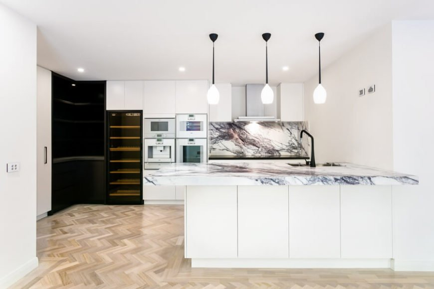 Bright kitchen with white walls and marble countertops and backsplash lighted by recessed ceiling lights.
