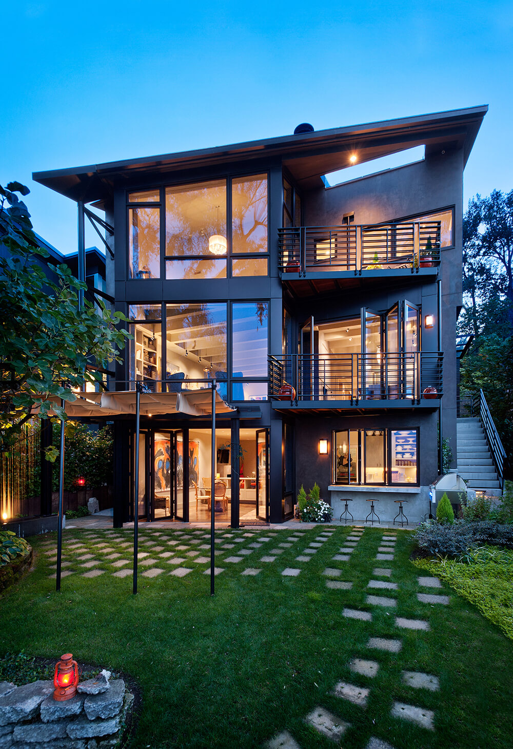 Viewed from the richly landscaped back yard, we see the towering structure covered in glass on this side. The warm interplay of light and fresh air helps connect the interior to the environment.
