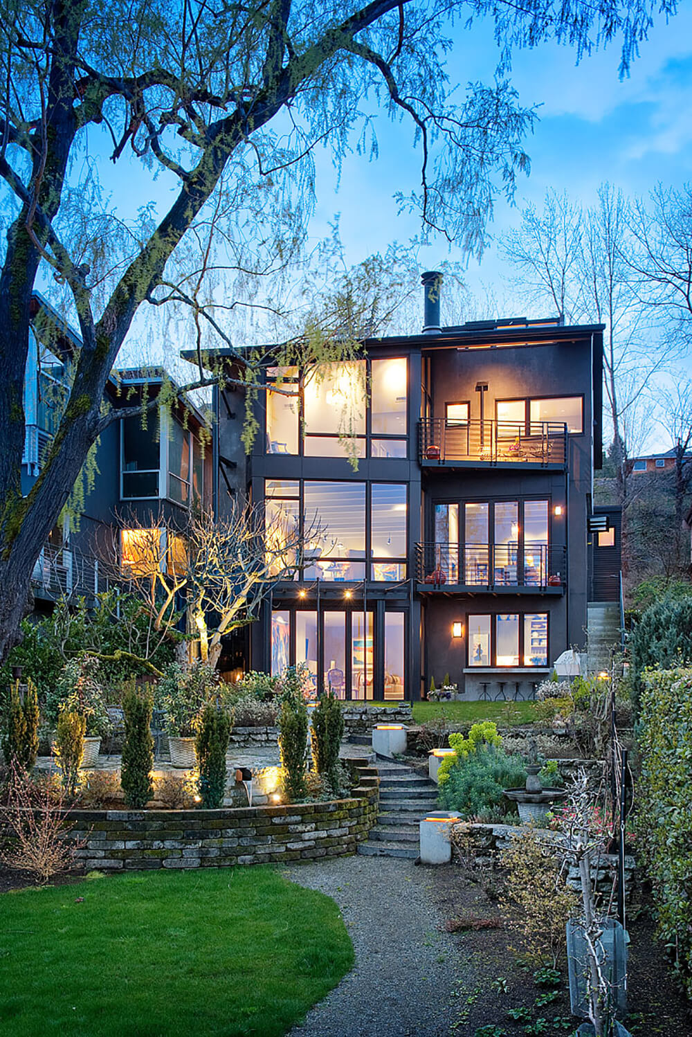 The landscape is immaculately designed, with tiers of stone brick separating layers of lawn, garden, and patio. The lighting design outdoors is as purposeful as the indoor component.