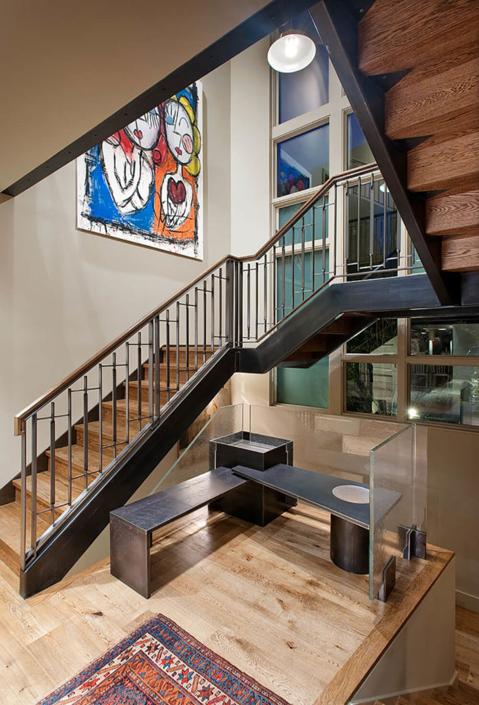 Here we reveal the incredible wood and steel staircase that connects the entire home. At center is a small sitting area comprised of steel and glass sculpted into a bench setting.