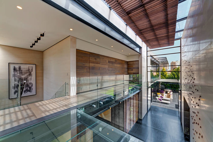 Returning to the central open lobby space, we see an upper catwalk hallway wrapped in glass balustrades, while the vast limestone wall at right is dotted with butterfly sculptures. Intricate details like this grant the large open space real character.
