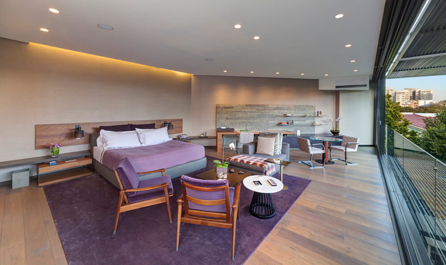 The primary bedroom is an expansive space, combining both the beige tone of limestone and the warm wood textures seen in the nearby family room. Bursts of purple appear courtesy of a large area rug, chairs, and bedding. This entire space overlooks the backyard landscape, sheltered by shade louvers.