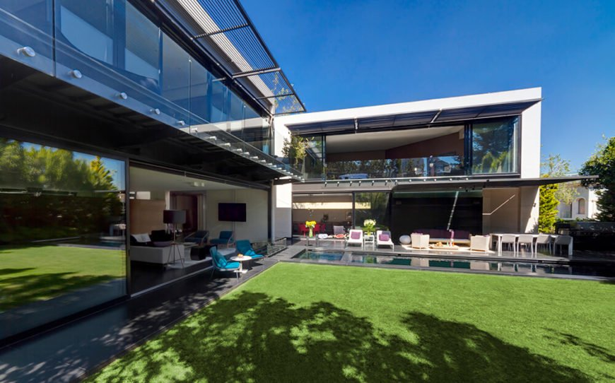 With the glass panels retracted fully, we can see into the living room at left and the primary bedroom at center, on the upper level. The malleability of the exterior design helps define this open interaction with the outdoors.