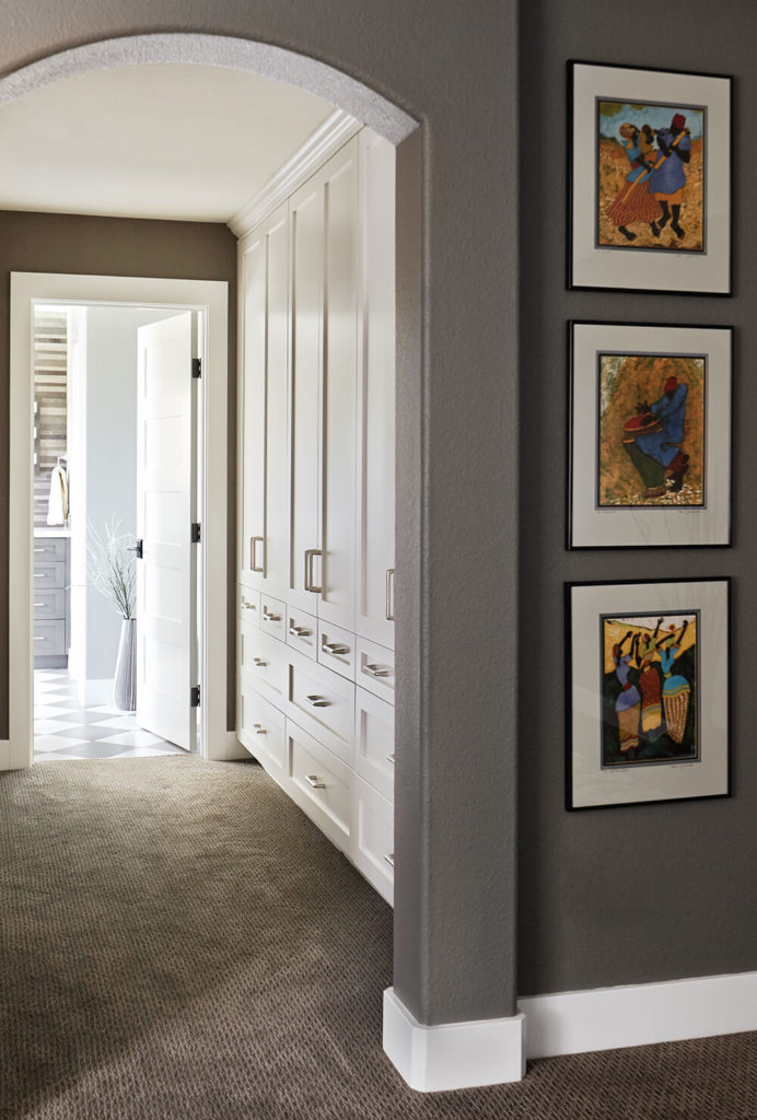 The primary bedroom connects to the bathroom by way of an open closet space flush with storage options along the right wall. White cabinetry and drawers reach from floor to ceiling for the ultimate in discreet storage.