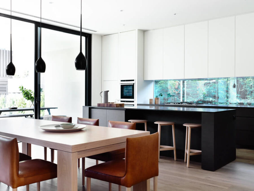 Contemporary kitchen with white walls and cabinetry along with black countertops and a center island featuring a breakfast bar and a dine-in table set.