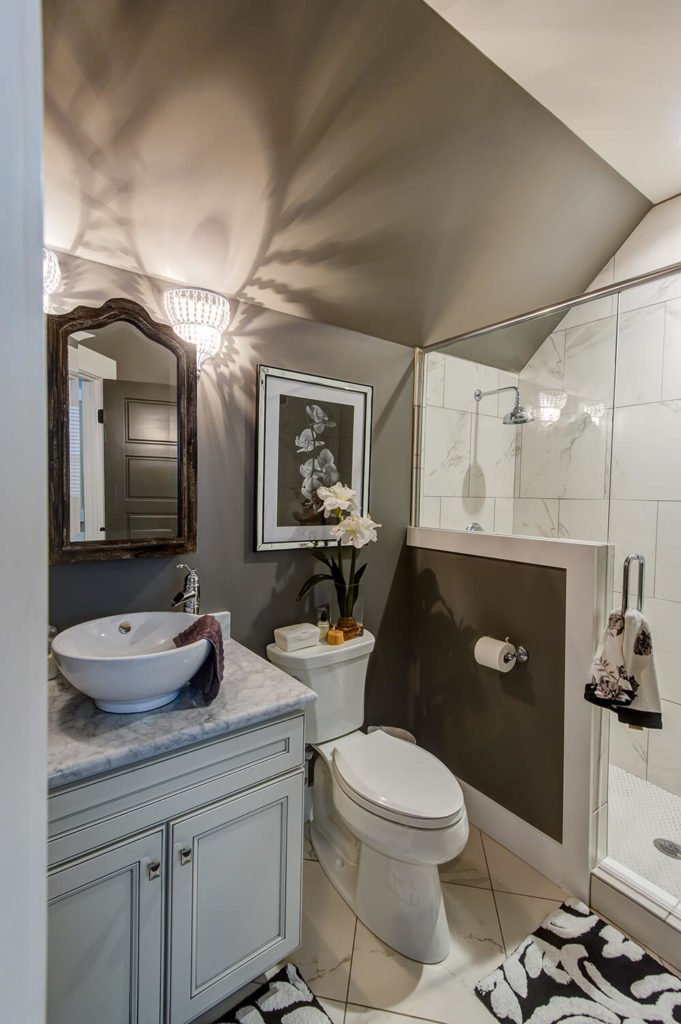 Entering into the bathroom, you'll notice an walk-in shower, tiled floors, and a nifty wash basin. The three elements combine to provide an elegant, functional lavatory.