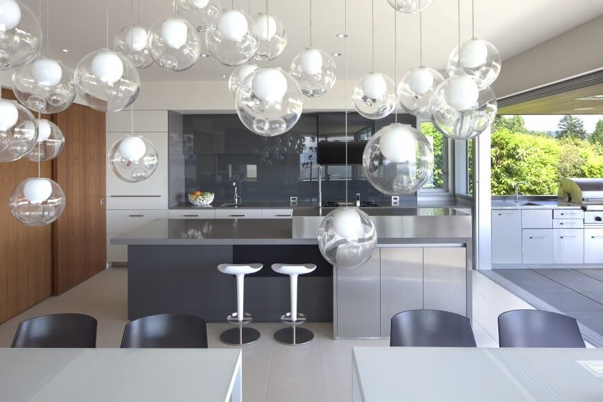Modern kitchen with smooth solid countertops and a gray backsplash styled by multiple pendant lights.