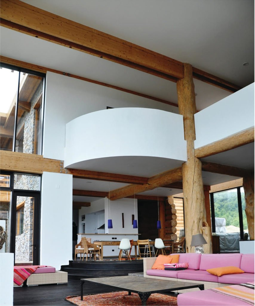 The second floor catwalk overlooks this sprawling open space, flush with the contrast between natural wood, white walls, and black stained flooring. Exposed beams criss-cross the design for a hybrid rustic-modern look.