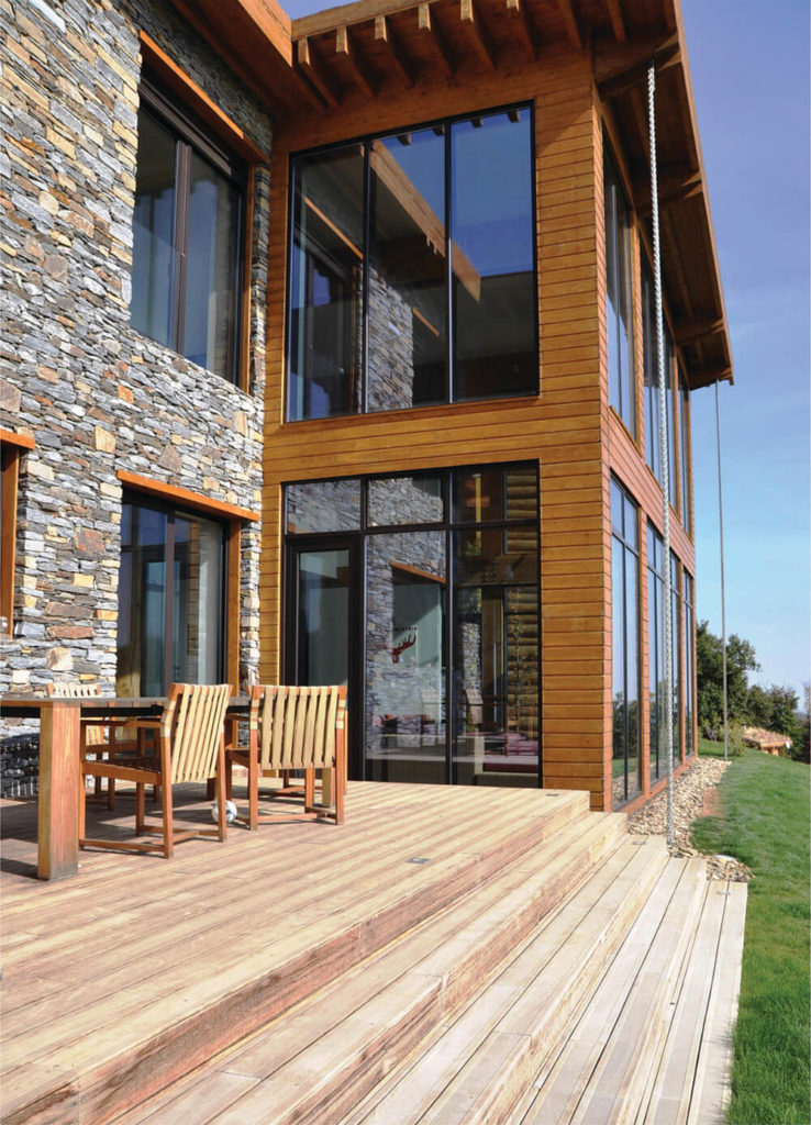 Approached on the rear side, we see a massive natural wood deck, complementing and contrasting with the rich timber and stone construction. Massive windows facilitate and openness of design.