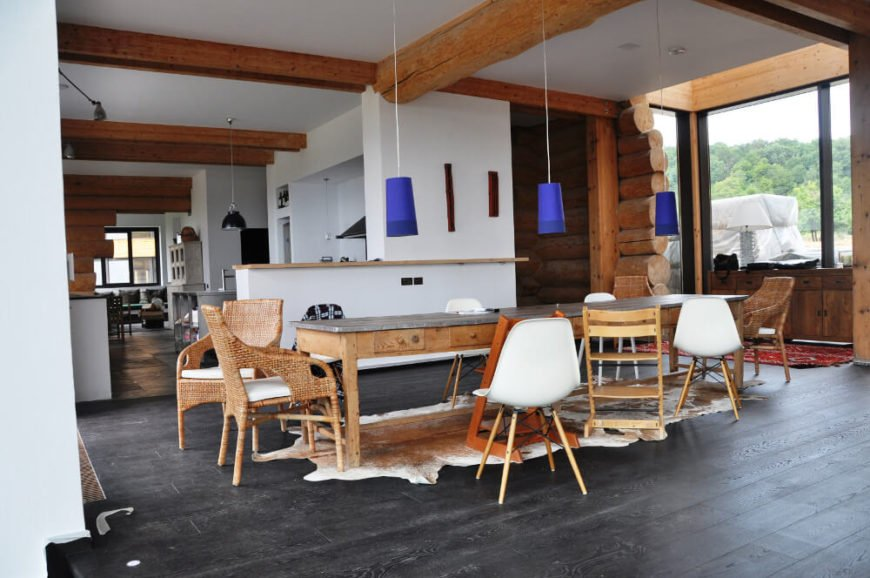 The dining room centers on a lengthy rustic style table, surrounded by an assortment of traditional and contemporary chairs in varying styles. The galley style kitchen extends to the left.
