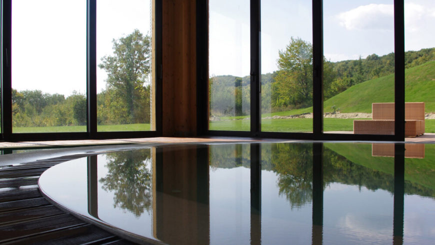 With a low view across the pool, we can see the landscape unfurling through the full height glass. The windows create a seamless visual transition to the outdoors, helping cement the home in its environment.