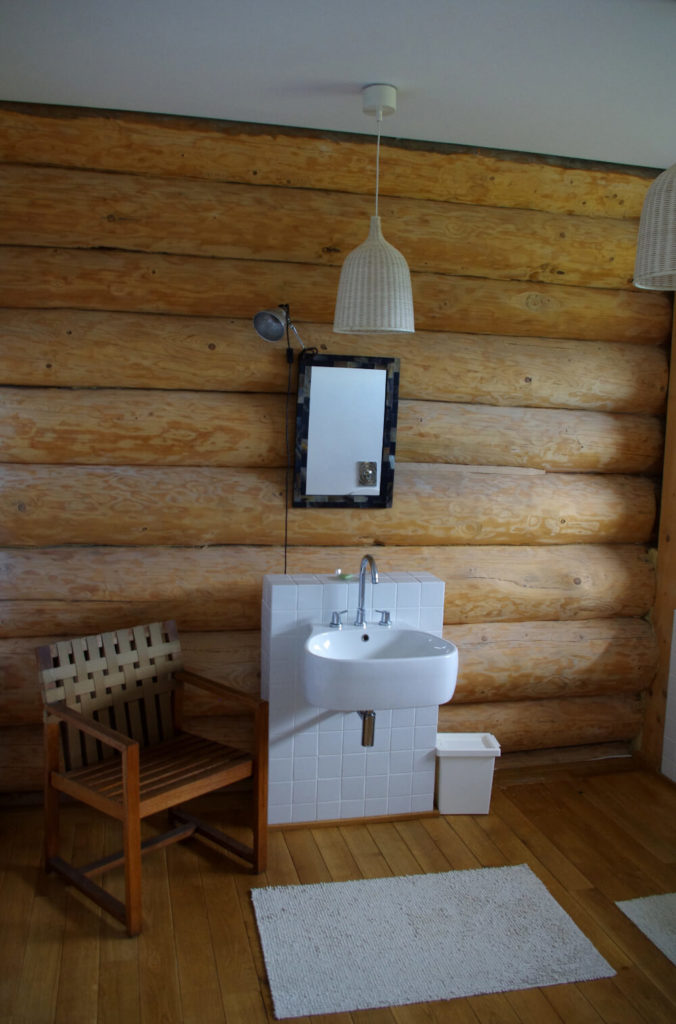 Here's one of the bathrooms, another exercise in elegant restraint. The floating sink is mounted to a small slab of white tile against the log wall, with only a small mirror and pair of pendant lights above, and a wood chair to the side.