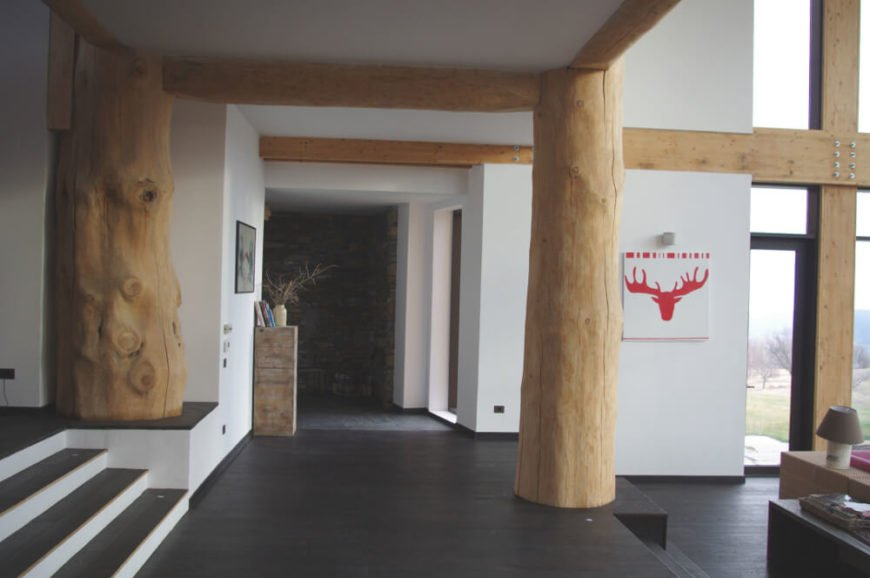 """To the side, we can see the magnificent natural wood pillars supplementing the exposed wood beams, cementing the """"cabin-like"""" look of the home and adding a stark contrast to the modern style."""