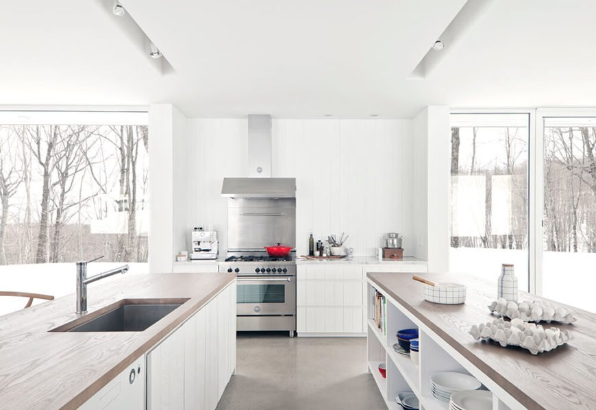 The kitchen spikes its all-white surroundings with stainless steel appliances and subtle recessed lighting. The island at right features an abundance of built-in storage.