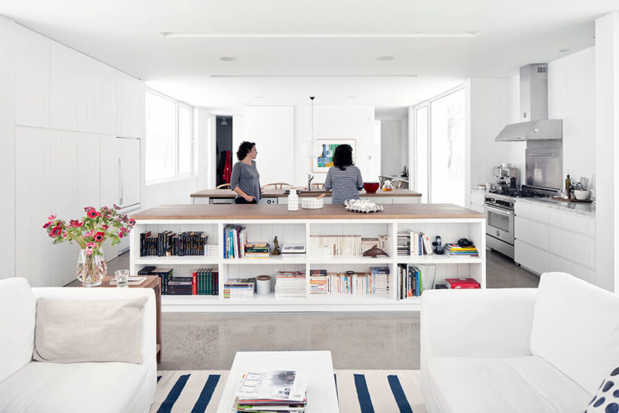 Moving back into the living room part of the open plan space, we can see a pair of white sofas on a white and blue striped rug facing over a similarly white coffee table. The outer side of the kitchen island features shelving for books, helping differentiate the functions within this large room.